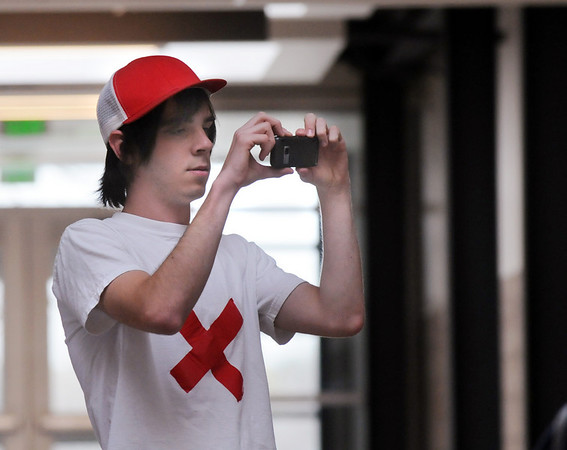 Broomfield High senior Max Lee takes pictures of students looking at his Day of Silence photography exhibit  for the gay and straight alliance at the school on Friday. <br /> <br /> April 16, 2010<br /> Staff photo/David R. Jennings