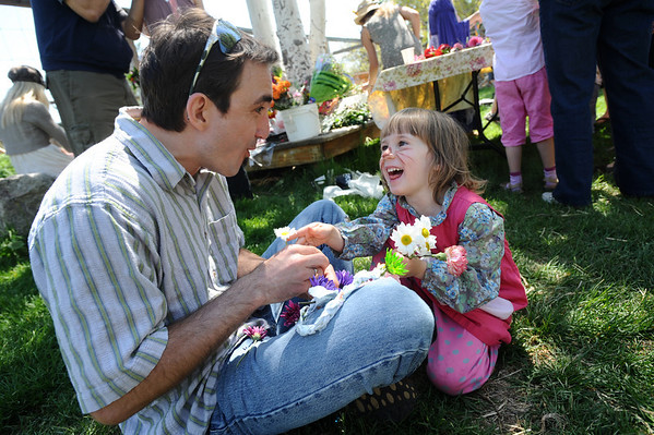 MAYPOLE01<br /> Alex O'Connor, 4, right, gets help from her dad, Darren, while making a flower crown at the May Faire held at the Boulder Waldorf Kindergarten on Friday morning.<br /> Photo by Marty Caivano/Camera/May 21, 2010