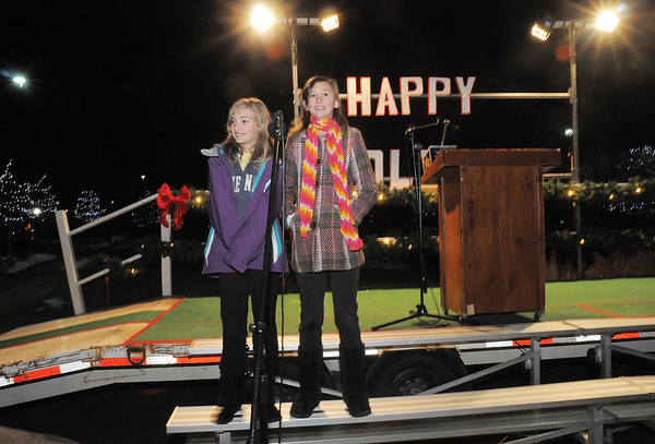 Aspen Creek Trio members Jenna Ammidown, 11, left, sings with Emiko Boyer, 11, during the tree lighting ceremony at the George Di Ciero City and County Building on Friday. Brooke Ammidown, 8, accompanied on the piano. <br /> <br /> December 2, 2011<br /> staff photo/ David R. Jennings