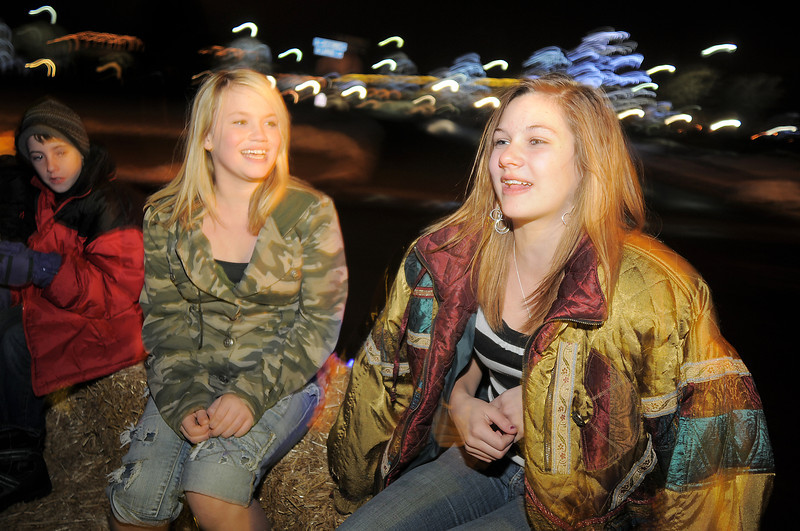 Mellissa Prater, 13, left, and Kassy Urbancic, 14, Westlake students, sing Christmas carols while on the hayride during the tree lighting ceremony at the George Di Ciero City and County Building on Friday.<br /> <br /> December 2, 2011<br /> staff photo/ David R. Jennings