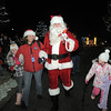 Santa is escorted by Dana Cabot to the tree lighting ceremony after arriving via helicopter at the George Di Ciero City and County Building on Friday.<br /> <br /> December 2, 2011<br /> staff photo/ David R. Jennings