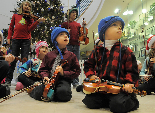 Simon Walker, 3, center, and his brother Casey, 5, prepare to play with the Suzuki Violin Students during the tree lighting ceremony at the George Di Ciero City and County Building on Friday.<br /> <br /> December 2, 2011<br /> staff photo/ David R. Jennings