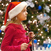 Katie Ziegler, 8, waits by the holiday tree to ply her violin with the Suzuki Violin Students during the tree lighting ceremony at the George Di Ciero City and County Building on Friday.<br /> <br /> December 2, 2011<br /> staff photo/ David R. Jennings