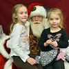 Izzy Schroeder, 6, left, and her sister Mia, 4, pose for pictures with Santa in the council chambers after the Mayor's Tree Lighting Ceremony at the George Di Ciero City and County Building on Friday.<br /> <br /> December 7, 2012<br /> staff photo/ David R. Jennings