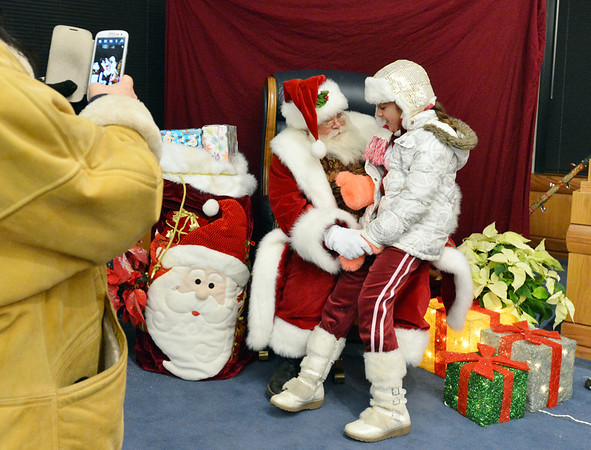 Jiovana DeBaise, 9, right, chats with Santa in the council chambers while her mother takes pictures during the Mayor's Tree Lighting Ceremony at the George Di Ciero City and County Building on Friday.<br /> <br /> December 7, 2012<br /> staff photo/ David R. Jennings