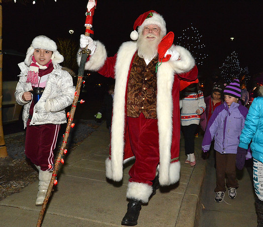 Santa is escorted by Jiovana DeBaise, 9, left, after he arrived via helicopter during the Mayor's Tree Lighting Ceremony at the George Di Ciero City and County Building on Friday.<br /> <br /> December 7, 2012<br /> staff photo/ David R. Jennings