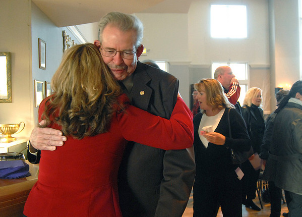 Julie Massingill, left, acting director of FISH, left, hugs Frank Parks, FISH food bank manager, after the memorial service for Shirley McGuinness executive director of Broomfield F.I.S.H. at the Chateaux at Fox Meadows on Monday.<br /> <br /> January 18, 2010<br /> Staff photo/David R. Jennings
