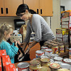 BE1125food07<br /> Indigo Armon, 6, holds a shopping bag for Mindy Harlan to put food in the bag as they help fill 220 Thanksgiving food baskets for Federal Heights Elementary at Meridian Elementary School on Thursday.<br /> November 18, 2010<br /> staff photo/David R. Jennings
