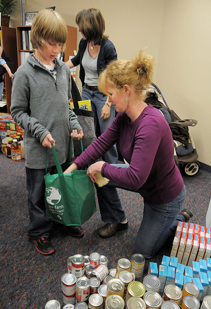 BE1125food02<br /> Hunter Brown, 10, student council member at Meridian Elementary School, holds a shopping bag for Lynn Grierson to put pumpkin pie cans into while helping fill 220 Thanksgiving food baskets for Federal Heights Elementary at Meridian on Thursday.<br /> November 18, 2010<br /> staff photo/David R. Jennings