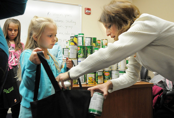BE1125food05<br /> Indigo Armon, 6, left, a student at Meridian Elementary School, holds a shopping bag as Jackie Ray puts cans of vegetables in the bag while  helping fill 220 Thanksgiving food baskets for Federal Heights Elementary on Thursday.<br /> November 18, 2010<br /> staff photo/David R. Jennings
