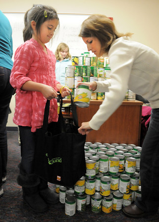 BE1125food03<br /> Meridian Elementary School student Grace Valdez, 9, left, holds a shopping bag while Jackie Ray places food in the bag while helping fill 220 Thanksgiving food baskets for Federal Heights Elementary on Thursday.<br /> November 18, 2010<br /> staff photo/David R. Jennings