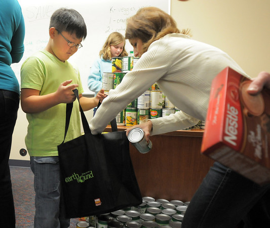 BE1125food01<br /> David Park, 9,  a student council member at Meridian Elementary School holds a shopping bag as Jackie Ray places cans of vegetables  into the bag while helping fill 220 Thanksgiving food baskets for Federal Heights Elementary at Meridian on Thursday.<br /> November 18, 2010<br /> staff photo/David R. Jennings