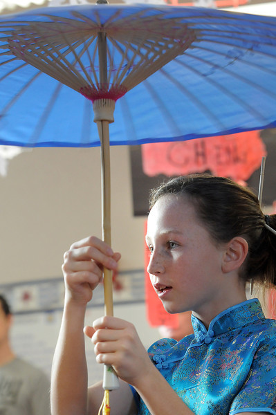 "Erin Hohnstein twirls a parasol for Vietman's Tet celebration during Meridian Elementary School fifth grader's winter holiday celebrations around the world on Thursday.<br /> More photos please see  <a href=""http://www.broomfieldenterprise.com"">http://www.broomfieldenterprise.com</a><br /> December 15, 2011<br /> Staff photo/ David R. Jennings"