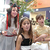 "Katelyn Adams, left, Taylor Ballain and Sophia Steen, while eating cookies, watch another class sing during Meridian Elementary School fifth grader's winter holiday celebrations around the world on Thursday.<br /> More photos please see  <a href=""http://www.broomfieldenterprise.com"">http://www.broomfieldenterprise.com</a><br /> December 15, 2011<br /> Staff photo/ David R. Jennings"