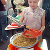 "Lauren Williams serves a Chinese dish during Meridian Elementary School fifth grader's winter holiday celebrations around the world on Thursday.<br /> More photos please see  <a href=""http://www.broomfieldenterprise.com"">http://www.broomfieldenterprise.com</a><br /> December 15, 2011<br /> Staff photo/ David R. Jennings"
