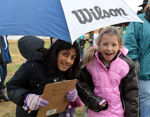 Aisha Prasad, 9, left, and Alexandra Nowakowski, 9, peek from under an umbrella during the opening ceremony for the Metzger Farm Open Space on Saturday.<br /> November 10, 2012<br /> staff photo/ David R. Jennings