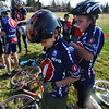 CROSS01<br /> Jackson Curry, left, 11, holds still while teammate Austin Sehnert, also 11, pins on his number at the Middle Cross Bike Fest at Manhattan Middle School on Wednesday. <br />  <br /> Photo by Marty Caivano/Camera/Nov. 11, 2009