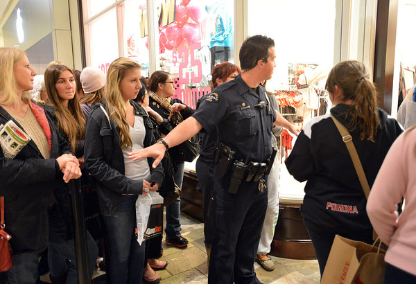 Broomfield Police officer helps control the crowd waiting to shop at Victoria Secrets during the Midnight Madness Black Friday event at FlatIron Crossing after midnight on Friday. <br /> November 24, 2012<br /> staff photo/ David R. Jennings