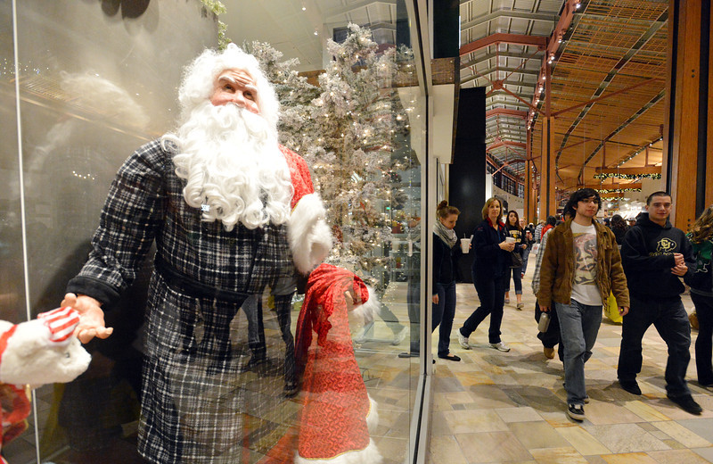 A Santa Claus mannequin on display while customers walk by during the Midnight Madness Black Friday event at FlatIron Crossing after midnight on Friday. <br /> November 24, 2012<br /> staff photo/ David R. Jennings