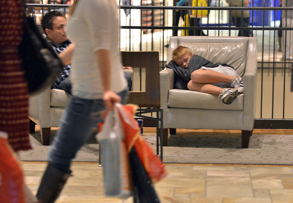 Ten year old Mason Veve from Erie, fell asleep while waiting with his parents for his 13 year old sister to finish shopping during the Midnight Madness Black Friday event at FlatIron Crossing after midnight on Friday. <br /> November 24, 2012<br /> staff photo/ David R. Jennings