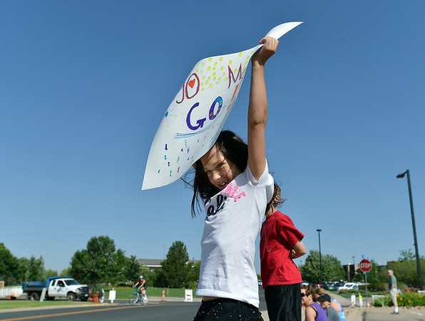 Kate Billesbach, 8, holds a sign up for her mother, Dawn, to seenear the finish line of  the Mini Haha Triathlon at the Broomfield Community Center.<br /> June 8, 2012 <br /> staff photo/ David R. Jennings