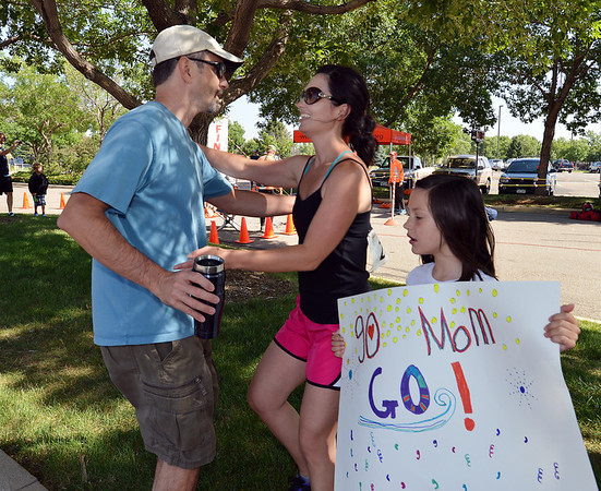 Dawn Bllesbach, center, greets her husband Jaryd with her daughter Kate, 8, at the finish line of the Mini Haha Triathlon at the Broomfield Community Center.<br /> June 8, 2012 <br /> staff photo/ David R. Jennings