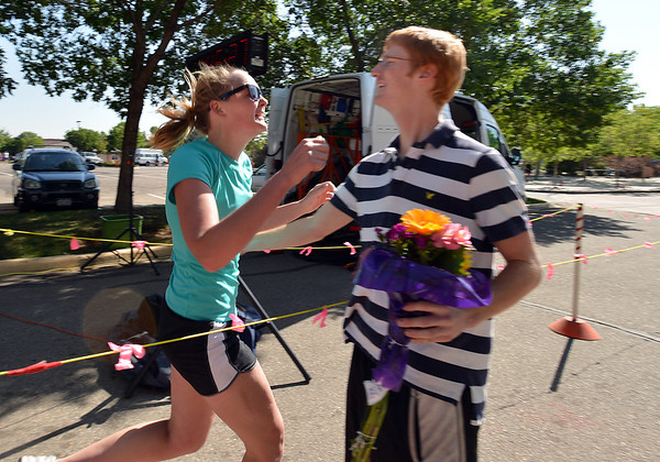 Amy Howard, left, is greeted by her boy friend Alex Eckel waitng to give her flowers at the finish line of the Mini Haha Triathlon at the Broomfield Community Center. This is Howard's first triatholn.<br /> June 8, 2012 <br /> staff photo/ David R. Jennings