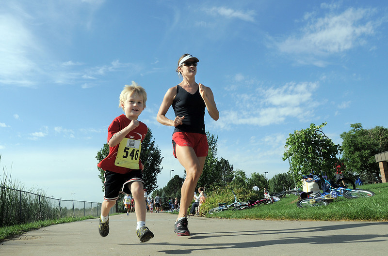 Jake Gustafson, 4, runs with his mother Jennifer on the running portion of the first MiniMini  HaHa for Kids triathlon at the Broomfield Community Center on Sunday.<br /> <br /> August 14, 2011<br /> staff photo/ David R. Jennings