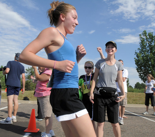 Madelaine McClain, 13, runs across the finish line with her mother Amy and sister Kedall, 9, cheering her on during the first MiniMini  HaHa for Kids triathlon at the Broomfield Community Center on Sunday.<br /> <br /> August 14, 2011<br /> staff photo/ David R. Jennings