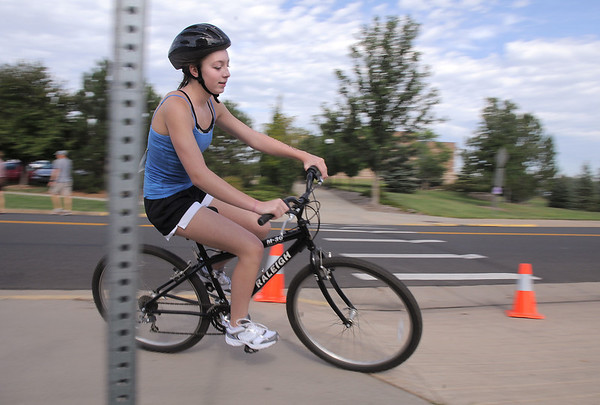 Madelaine McClain, 13, makes the hard right turn on the bicycle course during the first MiniMini  HaHa for Kids triathlon at the Broomfield Community Center on Sunday.<br /> <br /> August 14, 2011<br /> staff photo/ David R. Jennings