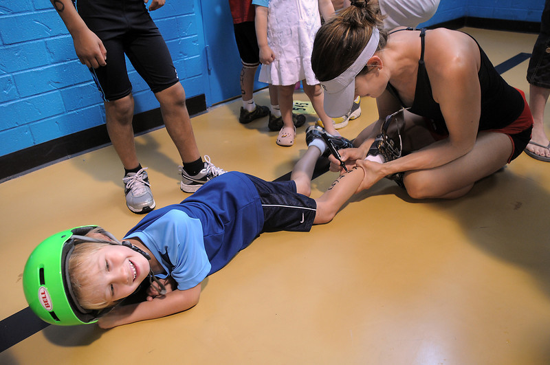 Brode Gustafson, 6, giggles while his mother, Jennifer, write his bib number on his leg during the first MiniMini  HaHa for Kids triathlon at the Broomfield Community Center on Sunday.<br /> <br /> August 14, 2011<br /> staff photo/ David R. Jennings
