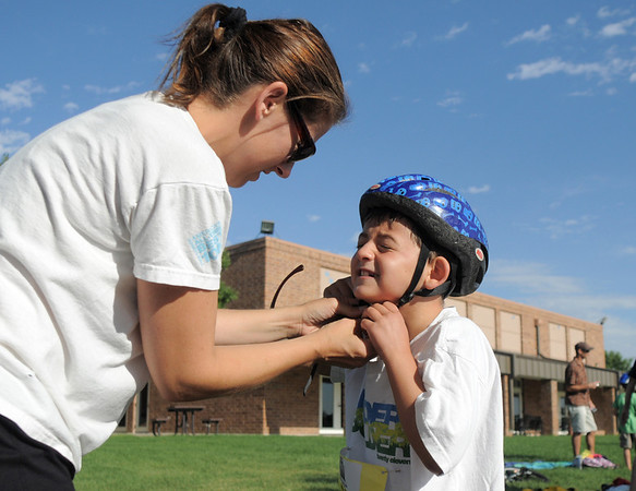 Dylan Barrett, 7,  with the help of his mother, Kira, puts on his bicycle helmet in the transition area during the first MiniMini  HaHa for Kids triathlon at the Broomfield Community Center on Sunday.<br /> <br /> August 14, 2011<br /> staff photo/ David R. Jennings