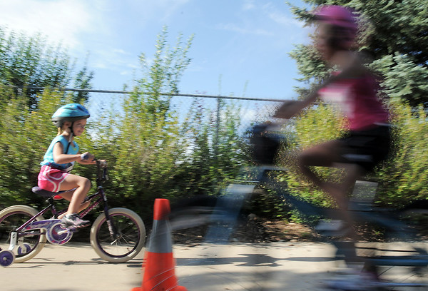 Bailey Stearns, 5, rides her bicycle in the second leg of the first MiniMini  HaHa for Kids triathlon at the Broomfield Community Center on Sunday.<br /> <br /> August 14, 2011<br /> staff photo/ David R. Jennings