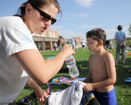 Kira Barrett, left, helps her son Dyaln in the transition area from swimming to riding his bicycle during the first MiniMini  HaHa for Kids triathlon at the Broomfield Community Center on Sunday.<br /> August 14, 2011<br /> staff photo/ David R. Jennings