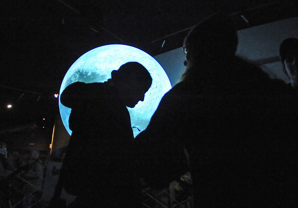 "MOON05<br /> An attendee is silhouetted in front of the ""Science on a Sphere"" globe at the University of Colorado Fiske Planetarium, which was illuminated to show the moon after NASA crashed a spacecraft into a deep crater at the moon's pole. About 200 Boulder County residents gathered at the planetarium and the Sommers-Bausch Observatory early Friday morning to watch the event.<br /> Photo by Marty Caivano/Camera/Oct. 9, 2009"
