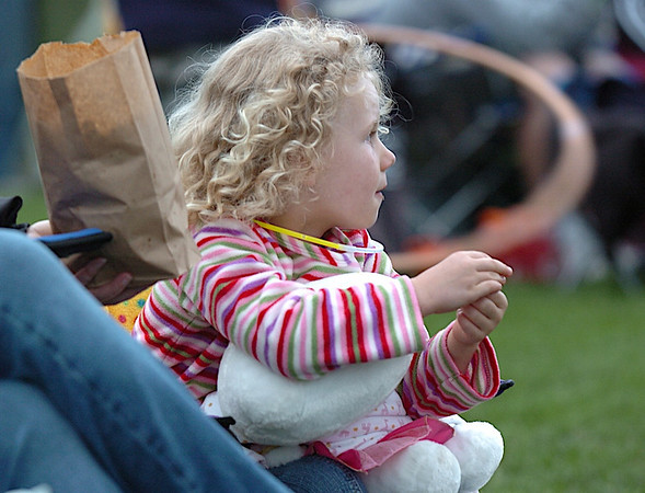"""Maya Walker, 5, eats some popcorn while waiting for the movie """"Kung Fu Panda"""" to start during Movies in the Park Saturday at County Commons Park.<br /> July 25, 2009<br /> staff photo/David Jennings"""