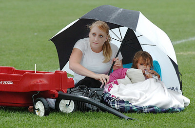"Kayla Clark and her daughter Avery, 2, take shelter under an umbrella as they wait for the movie ""Kung Fu Panda"" to start during Movies in the Park Saturday at County Commons Park. Kayla said that they missed the other movies because they were rained out.  So  they came prepared to wait out the weather. ""We weren't going to miss the movie."" she said. July 25, 2009 staff photo/David Jennings"