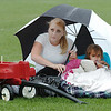"Kayla Clark and her daughter Avery, 2, take shelter under an umbrella as they wait for the movie ""Kung Fu Panda"" to start during Movies in the Park Saturday at County Commons Park.<br /> Kayla said that they missed the other movies because they were rained out.  So  they came prepared to wait out the weather. ""We weren't going to miss the movie."" she said.<br /> July 25, 2009<br /> staff photo/David Jennings"