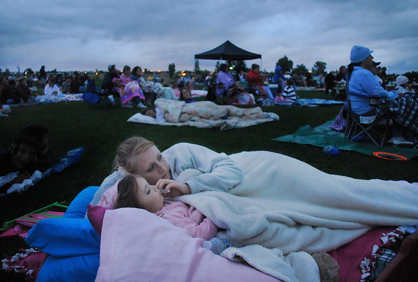 "Kayla Clark and her daughter Avery, 2, wrapped in blankets watch the movie ""Kung Fu Panda"" to during Movies in the Park Saturday at County Commons Park.<br /> July 25, 2009<br /> staff photo/David Jennings"