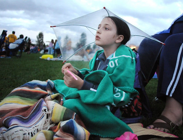 "Terina Patrick,  8, holds her glow stick under her clear umbrella while waiting for the movie ""Kung Fu Panda"" to start for Movies in the Park Saturday at County Commons Park.<br /> July 25, 2009<br /> staff photo/David Jennings"