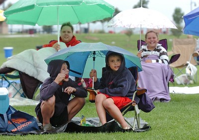 "Bobby Ziegler, 8, left, and Nick Spinuzzi, 8, take refuge under an umbrella while waiting for the movie ""Kung Fu Panda"" to start for Movies in the Park Saturday at County Commons Park. July 25, 2009 staff photo/David Jennings"