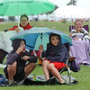 """Bobby Ziegler, 8, left, and Nick Spinuzzi, 8, take refuge under an umbrella while waiting for the movie """"Kung Fu Panda"""" to start for Movies in the Park Saturday at County Commons Park.<br /> July 25, 2009<br /> staff photo/David Jennings"""