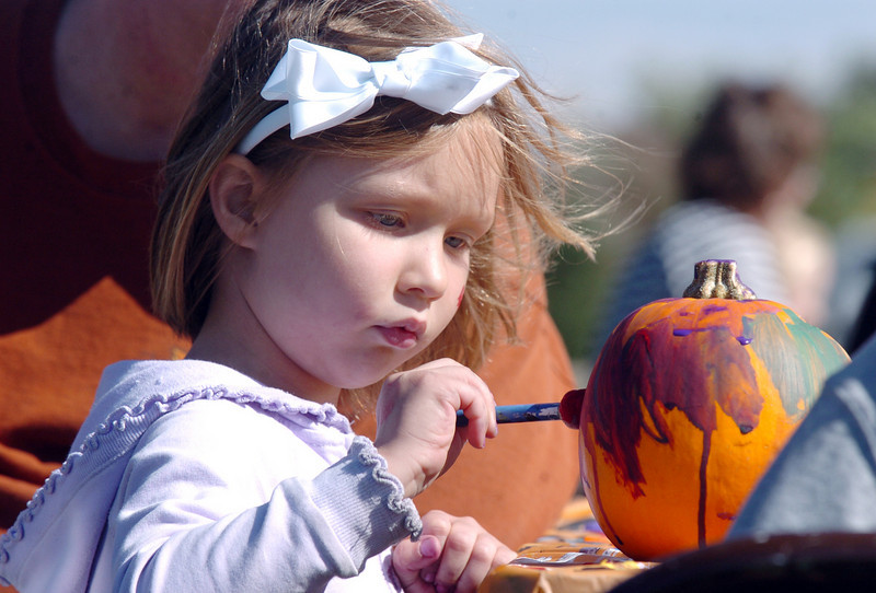 Emily Flaharty, 5, concetrates while painting a pumpkin during Mtn. View Elementary School's 30th anniversary celebration and fall festival on Saturday.<br /> October 9, 2010<br /> staff photo/David R. Jennings