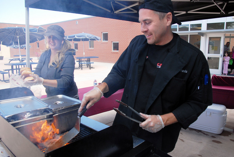 D.J. Demier, right, and Jessica Demier with CB & Potts, make hamburgers and hot dogs for participants in Mtn. View Elementary School's 30th anniversary celebration and fall festival on Saturday.<br /> October 9, 2010<br /> staff photo/David R. Jennings