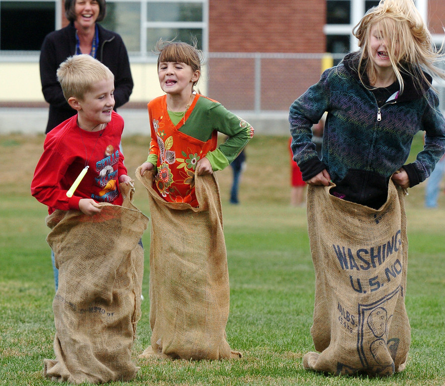 Harper Wood, 6, left, Lauren Wood, 9, and Aly Pratkelis, 8, compete in a sack race during Mtn. View Elementary School's 30th anniversary celebration and fall festival on Saturday.<br /> October 9, 2010<br /> staff photo/David R. Jennings