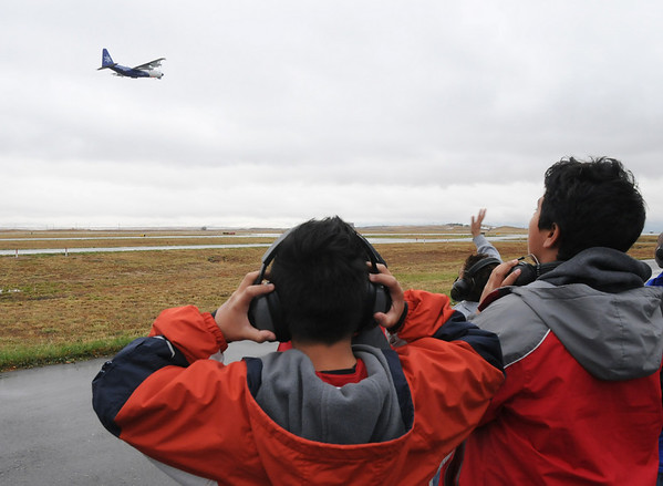 Johny Mendez, 10, left, and Saul Medellin, 12, from Vaughn Elementary School in Aurora, watch the NCAR C130 aircraft takeoff during a break in the tour of the NCAR Gulfstream V aircraft which is being outfitted for the HIPPO II reasearch project at the NCAR base at Rocky Mountain Metro Airport on Wednesay.<br /> <br /> October 21, 2009<br /> Staff photo/David R. Jennings