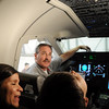 Brent Kidd, crew chief for the NCAR Gulfstream V aircraft  explains the cockpit  to Marcela Toledo, left, and her son Said Cisneros, 7, during tour of the aircraft which is being outfitted for the HIPPO II reasearch project at the NCAR base at Rocky Mountain Metro Airport on Wednesay.<br /> <br /> October 21, 2009<br /> Staff photo/David R. Jennings