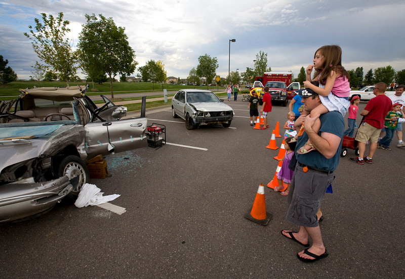 Jeff Warren and his daughter Abby, age 5, examine the remains of a car used in the 'Jaws of Life' demonstration by the North Metro Fire and Rescue during the National Night Out at the Broomfield County Commons on Aug. 3, 2010. Photo by Matt Kelley/for the Enterprise