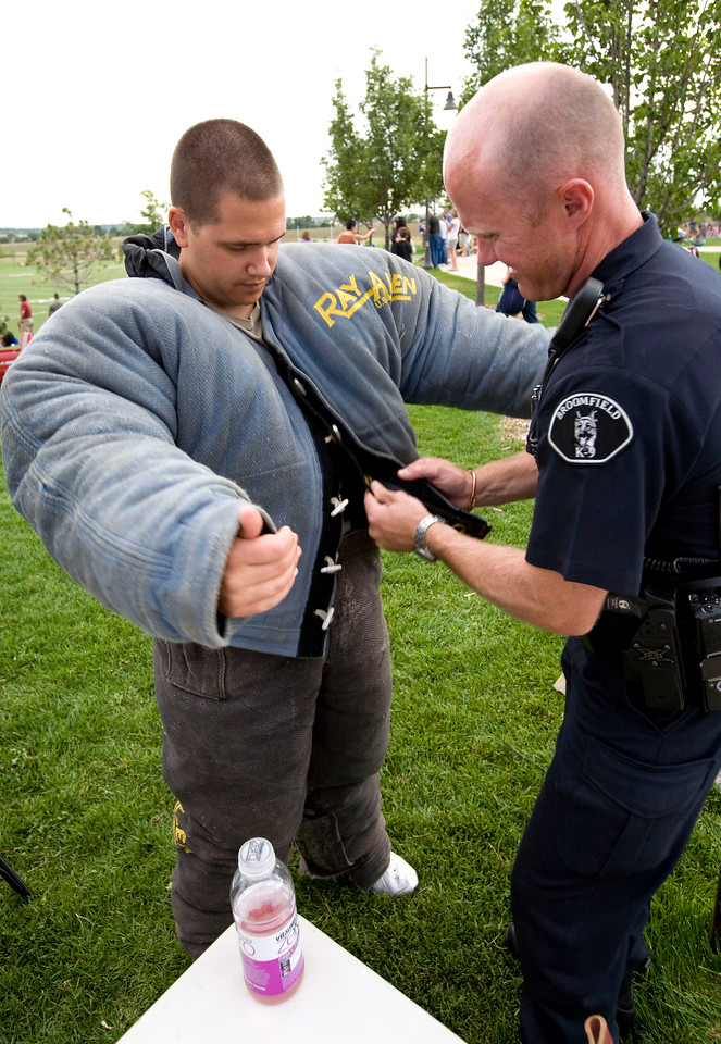 "Officer Jarrod Lang, playing the ""bad guy"",  puts on his dog protection armor with help from Officer Adrian Peeach before the canine demonstration during the National Night Out at the Broomfield County Commons on Aug. 3, 2010. Photo by Matt Kelley/for the Enterprise"