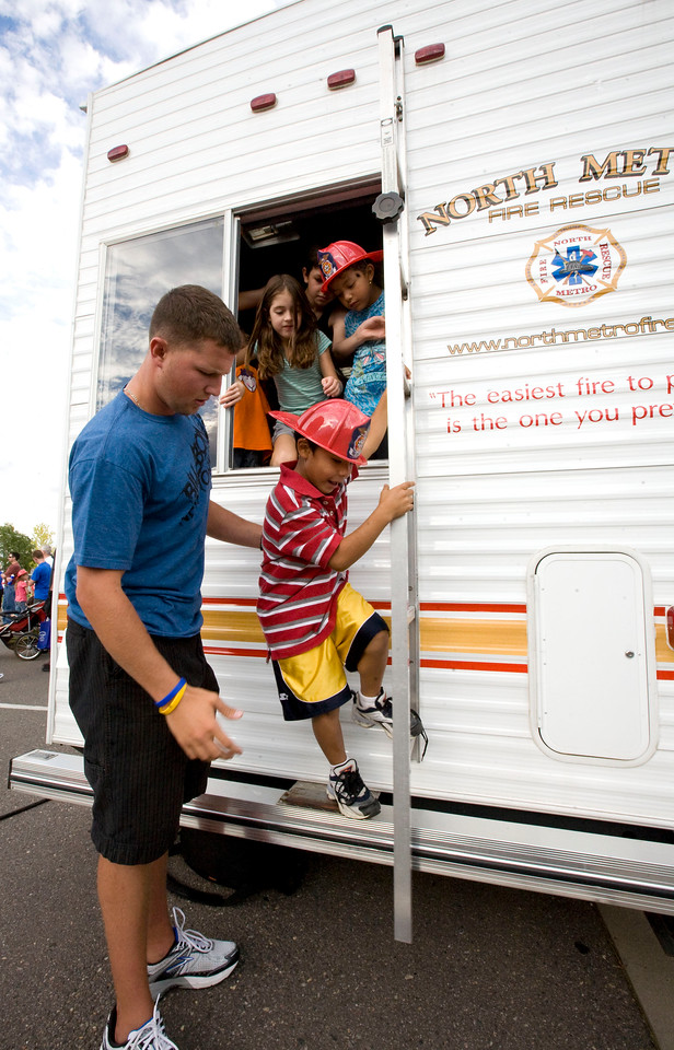 Volunteer Bryce Babcock, left helps Fransisco Aguero, 7, out of the North Metro Fire and Rescue Extrication and Smoke Trailer during the National Night Out at the Broomfield County Commons on Aug. 3, 2010.  PHoto by Matt Kelley/for the Enterprise